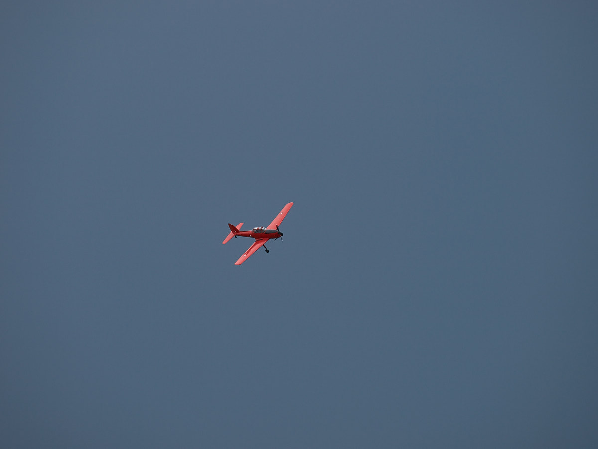 Red aircraft in right turn agains dark sky
