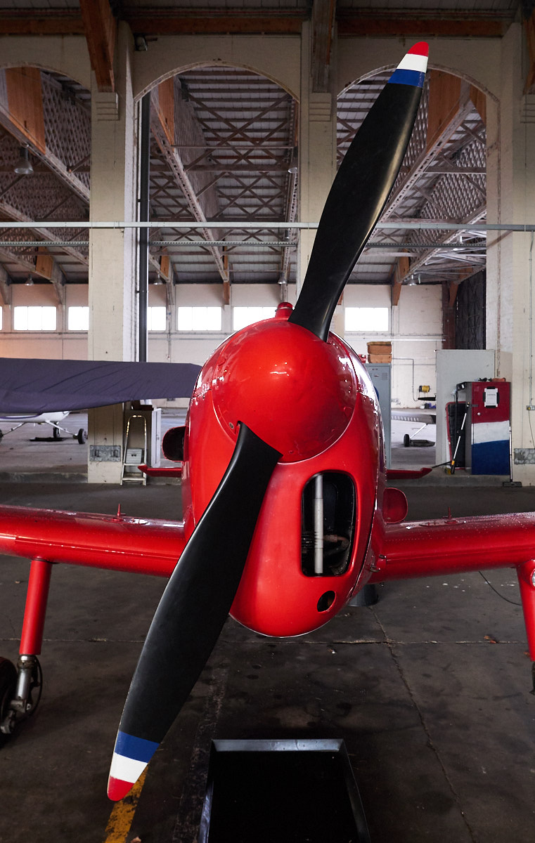 Aircraft propellor with red spinner and nose.