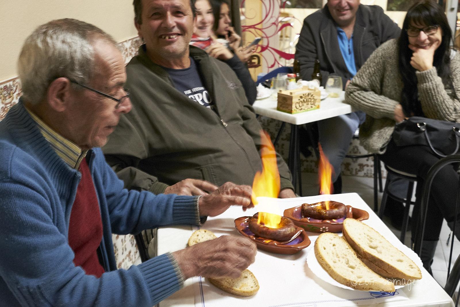2 men eat watch flaming chorizo, people watch in café.