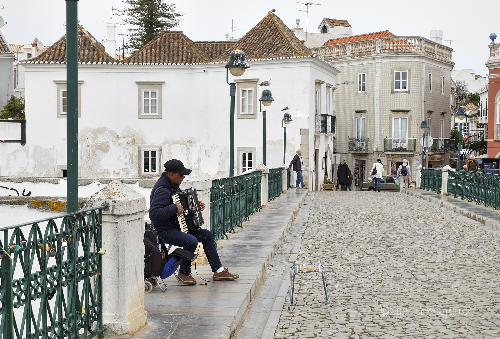An accordion player on the Roman bridge in Tavira, Portugal