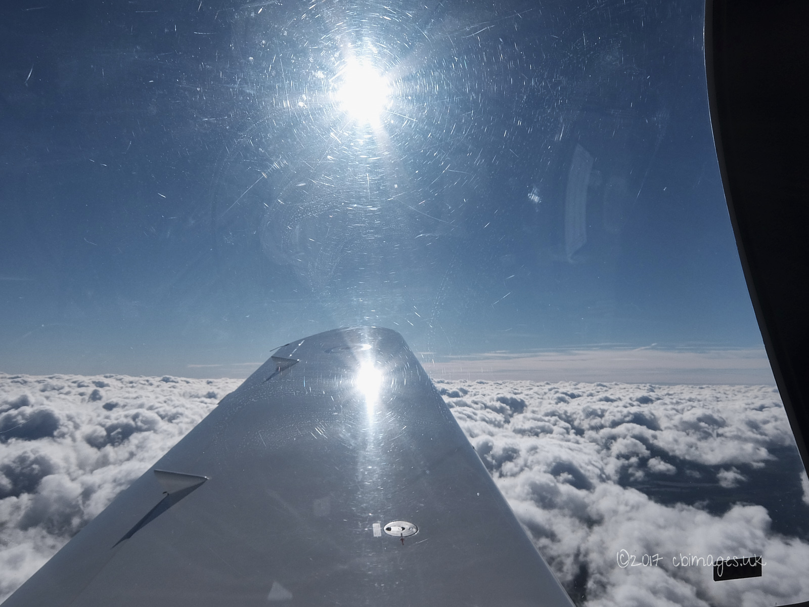 Aircraft wing and clouds with sun.