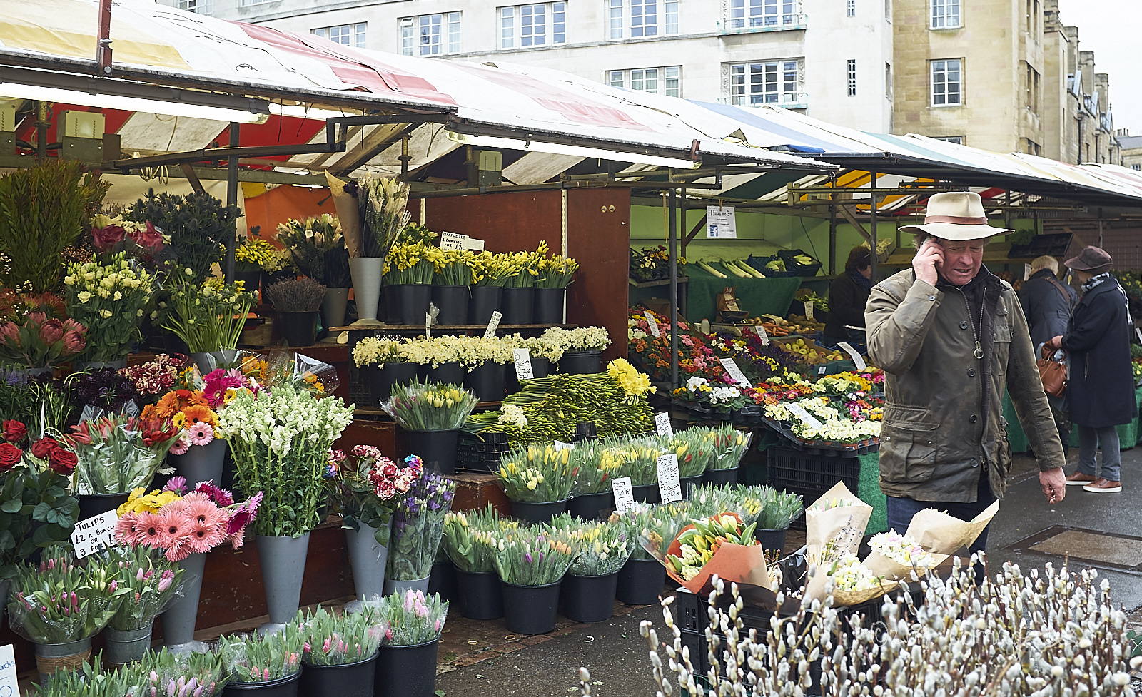 man in hat next to flower stall