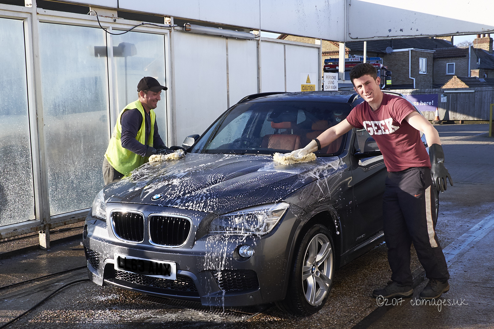 Two men wash a car