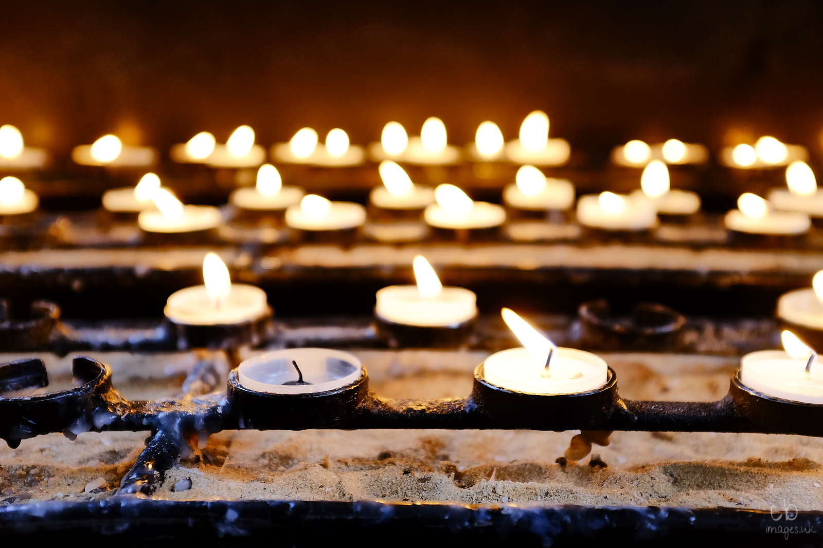 Votive candles in Bath Abbey with one extinguished