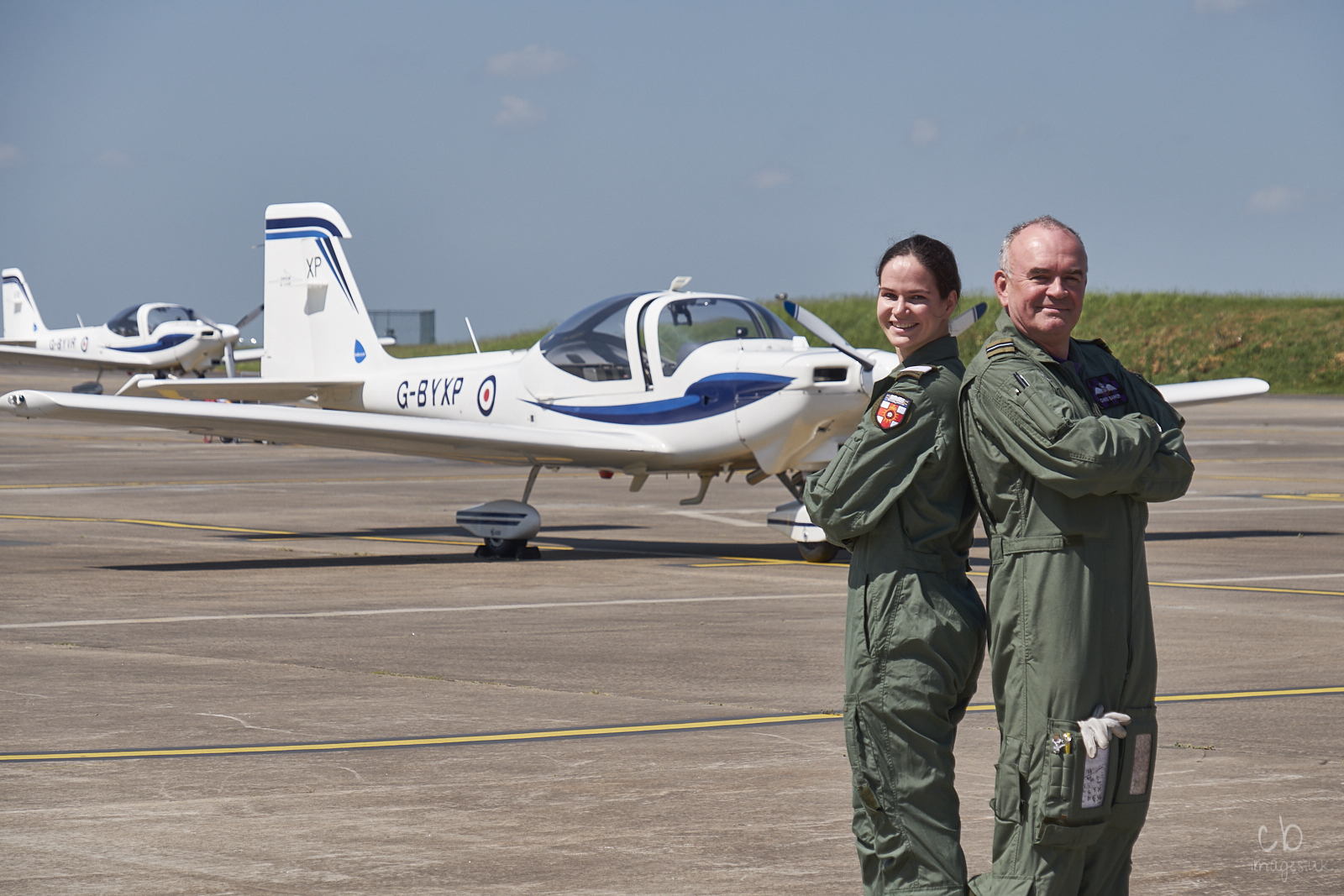 Two pilots stand back-to-back in front of a white aircraft