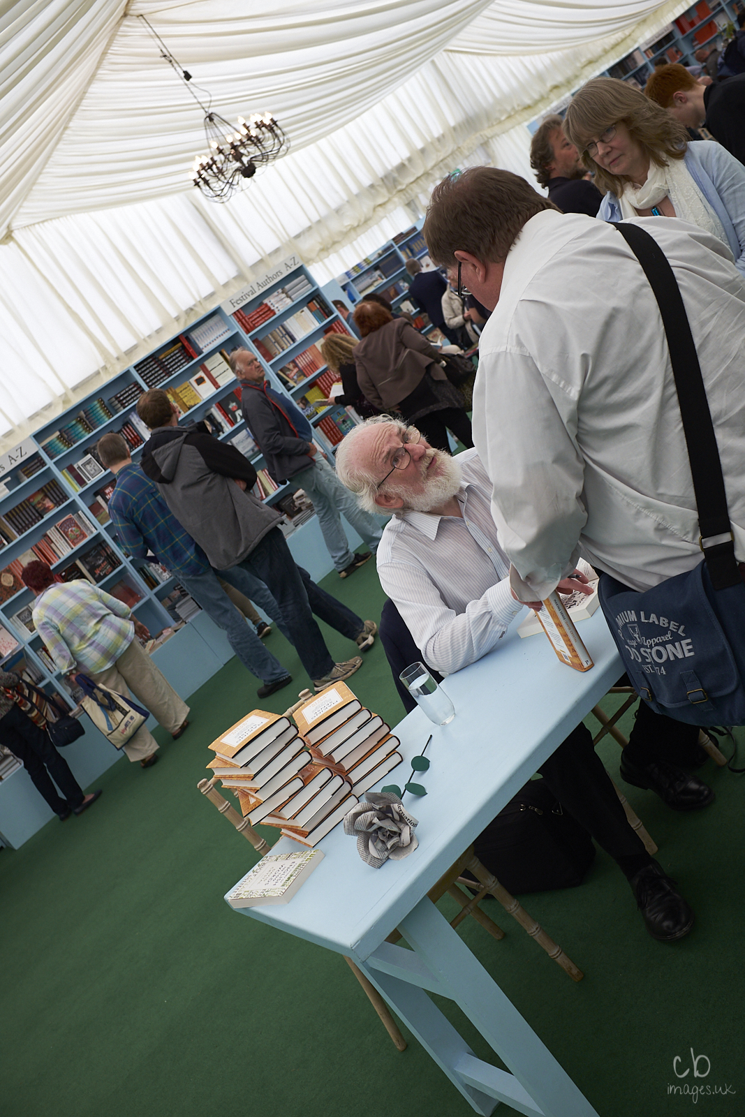 A white-haired author signs one of his books