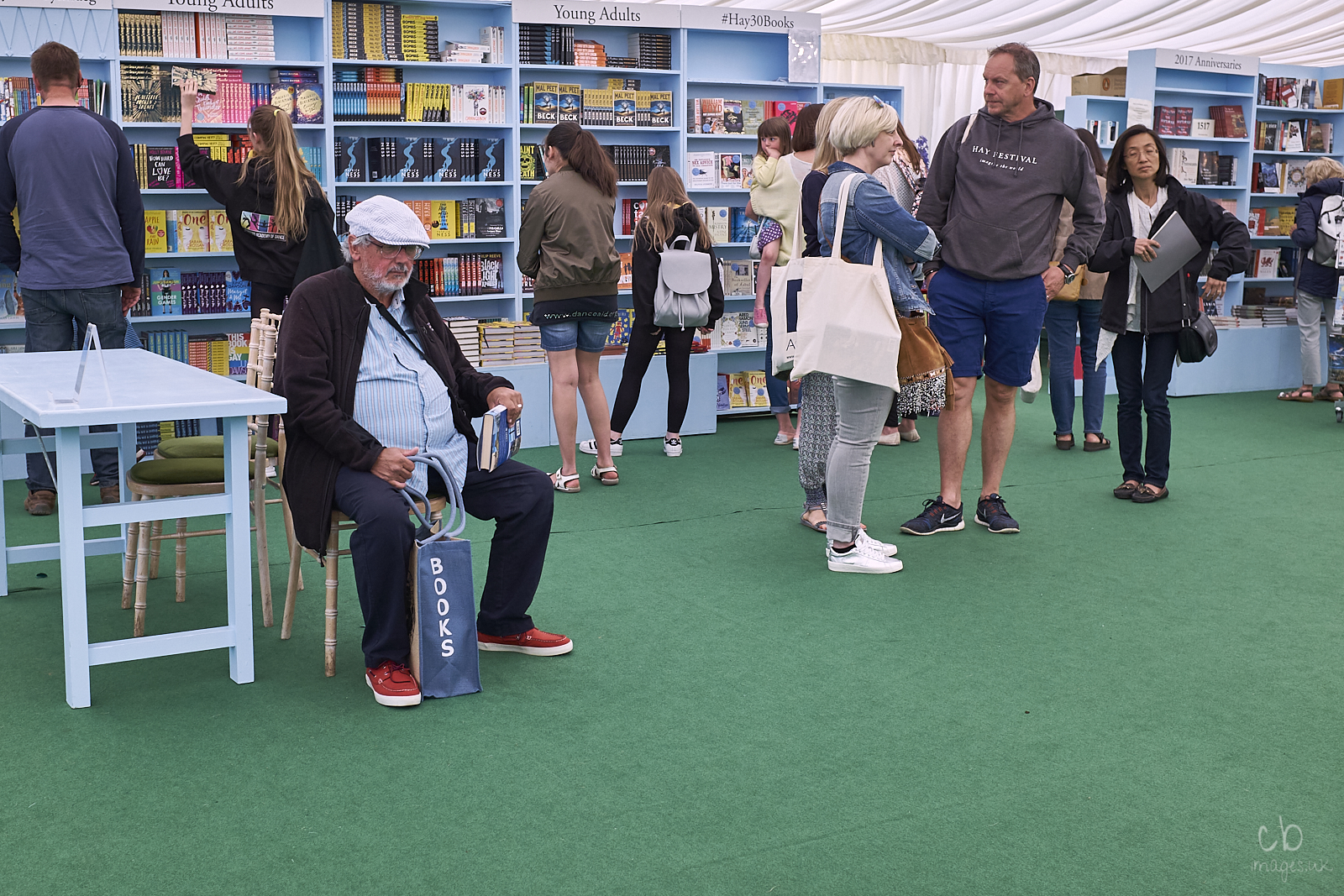 A man with a white cap sits in the book tent at Hay