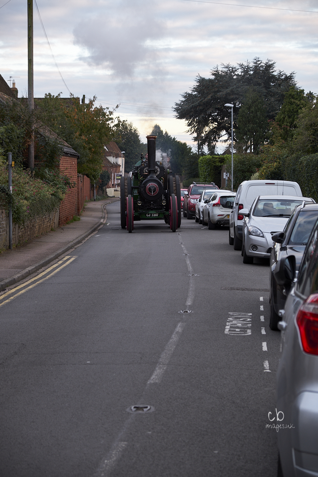 A steam traction engine approaches past a line of modern cars parked on the side of the street.