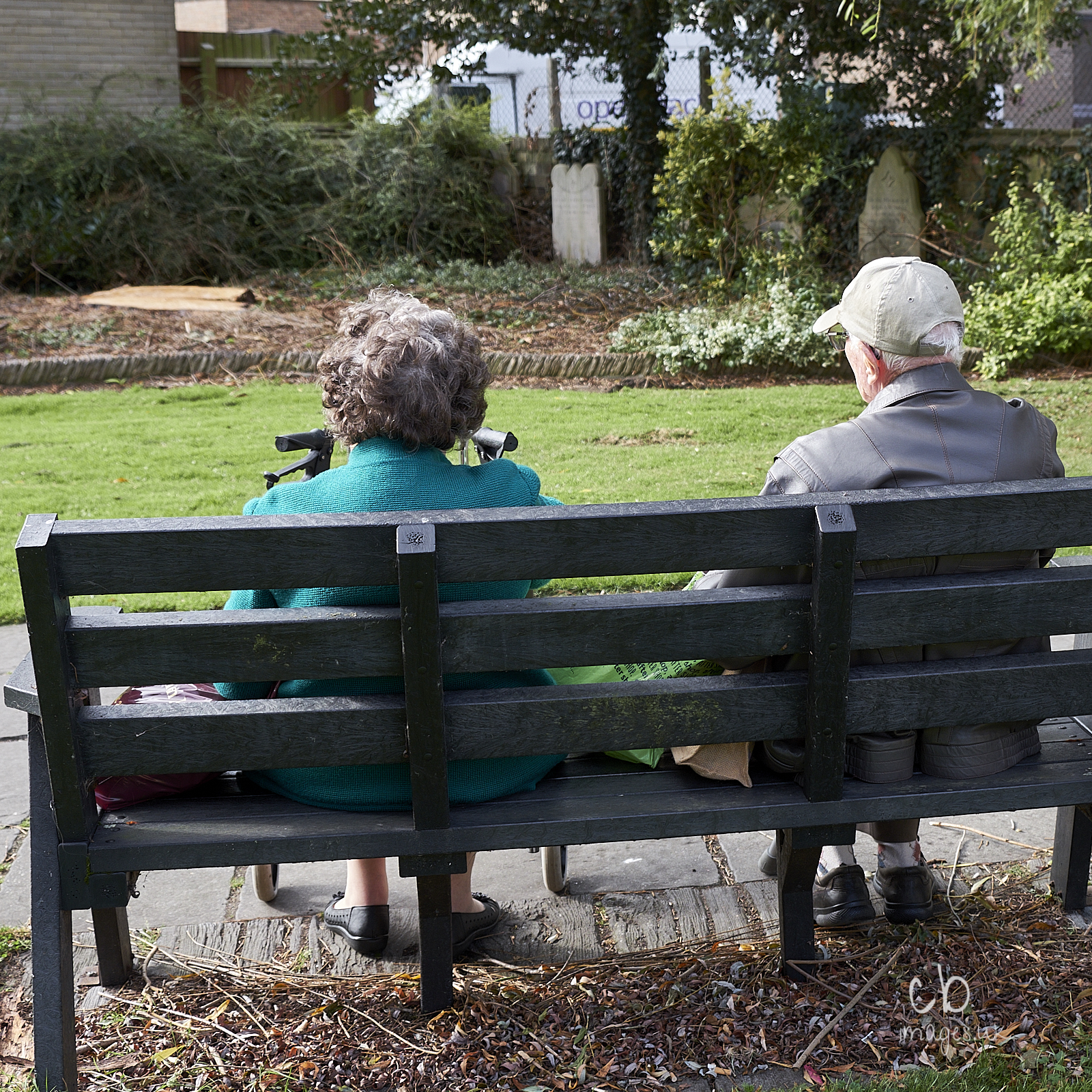 Two elderly individuals take a rest on a bench in a town in England