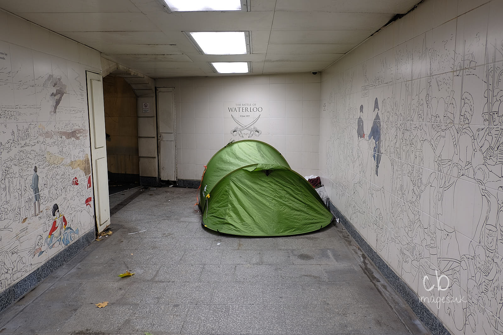 A green tent in a subway passage.