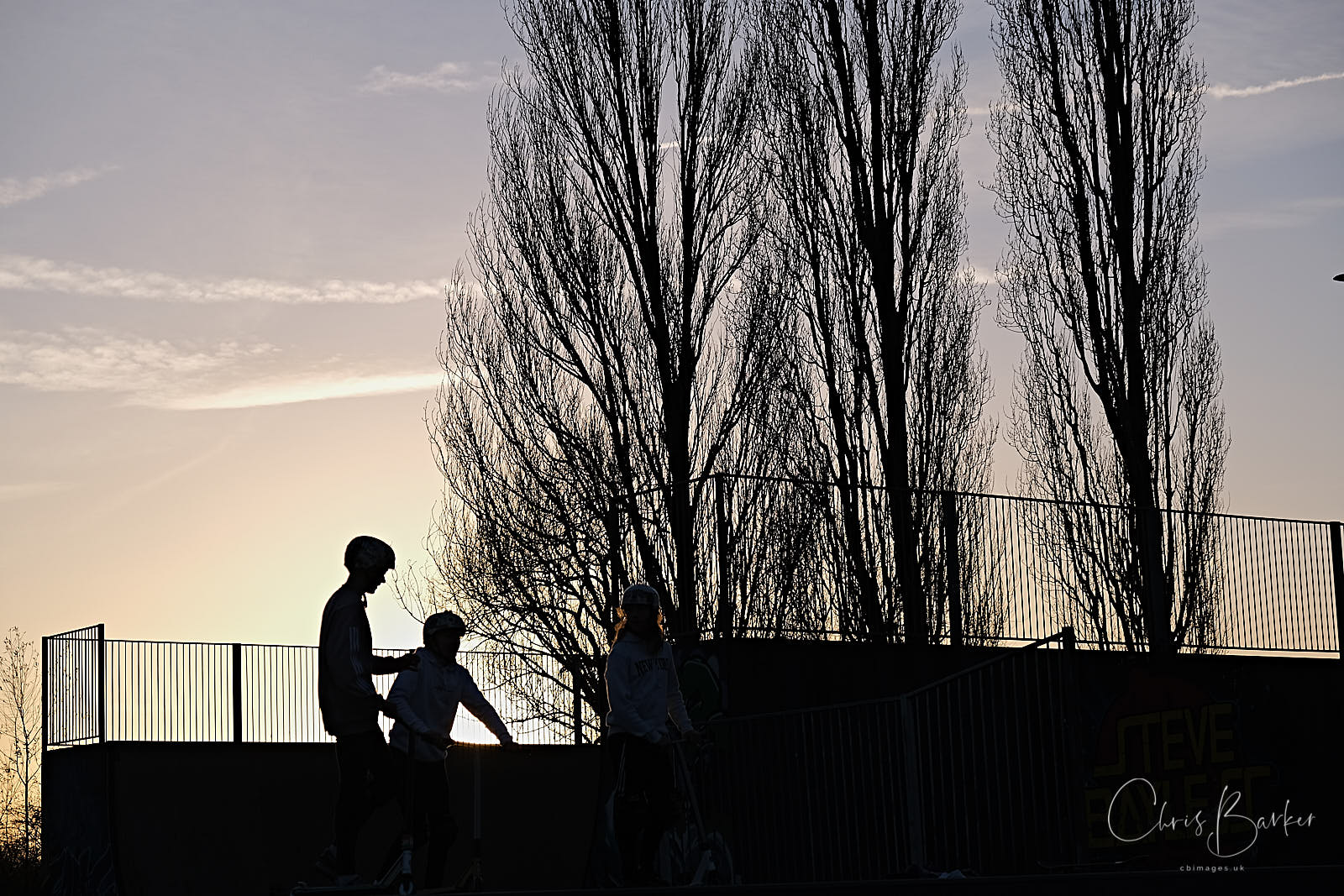 Silhouetted boys on half-pipe
