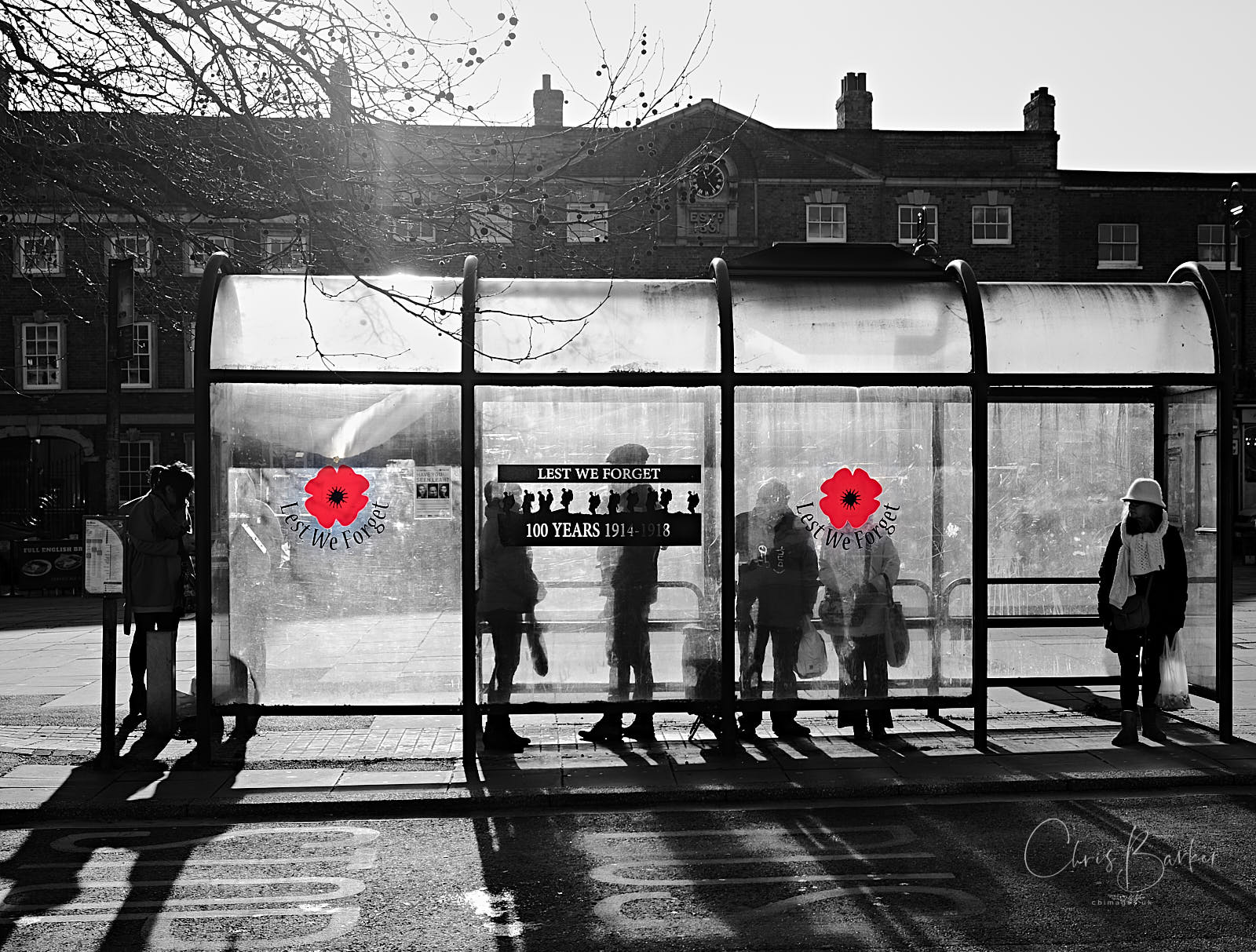 Silhouettes of people in a perspex bus shelter with red poppy designs on the perspex and Lest We Forget between