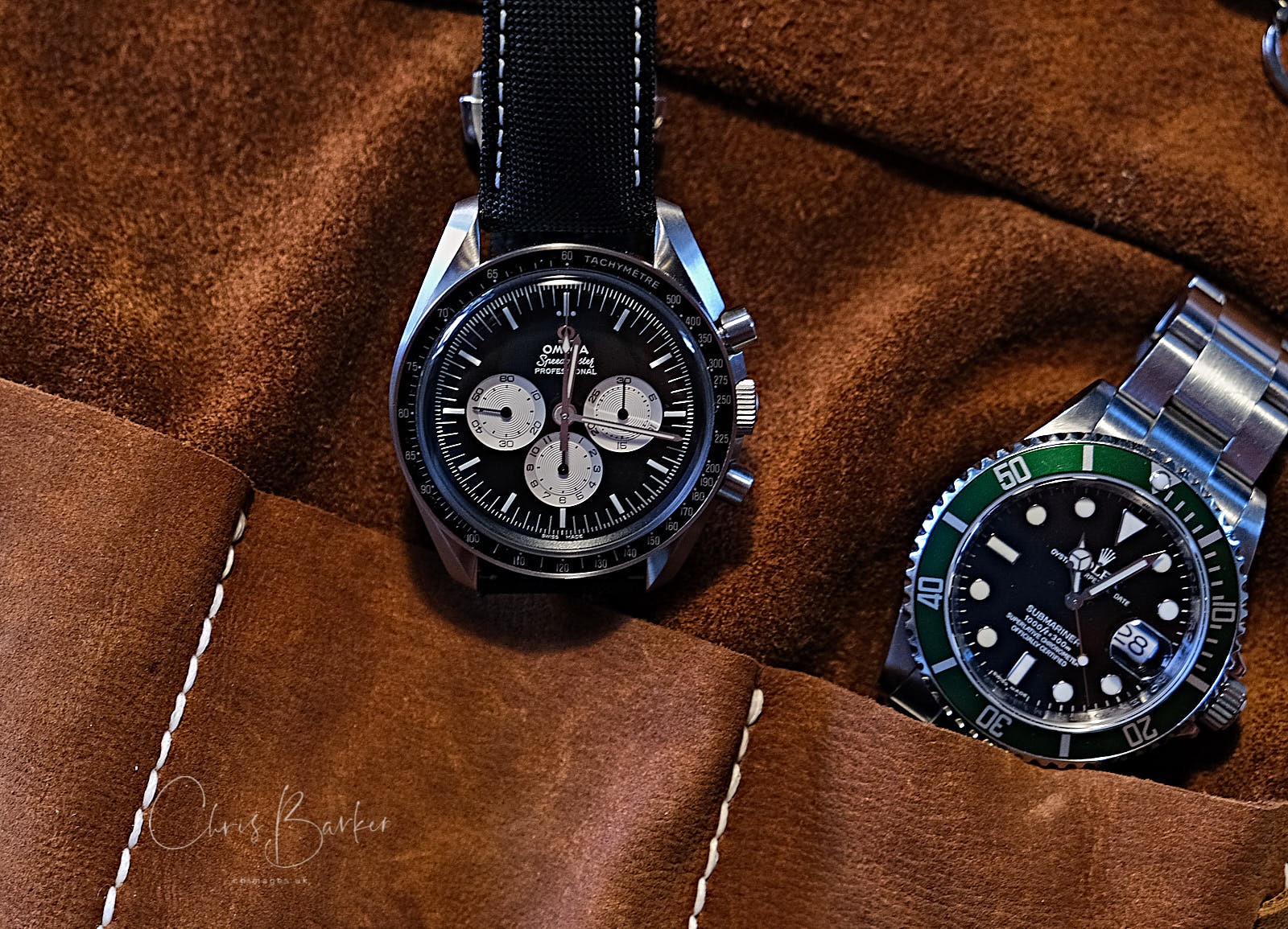 Two valuable watches close-up in a leather pouch.