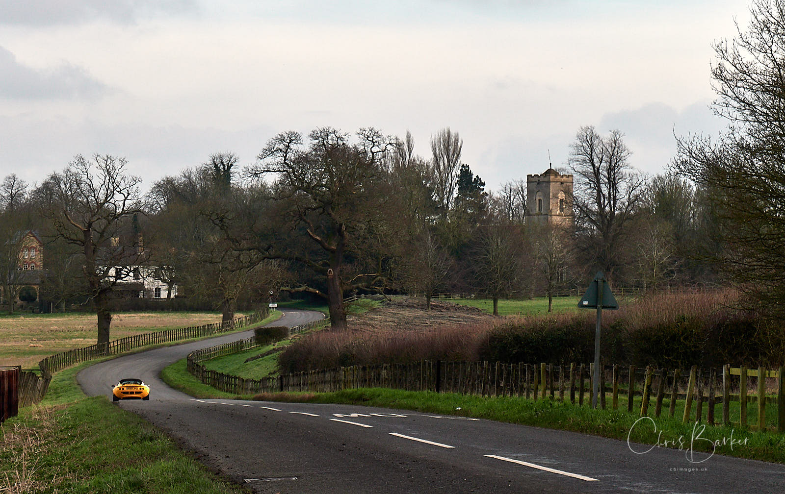 A yellow sports car on a road into a rural village with church tower visible