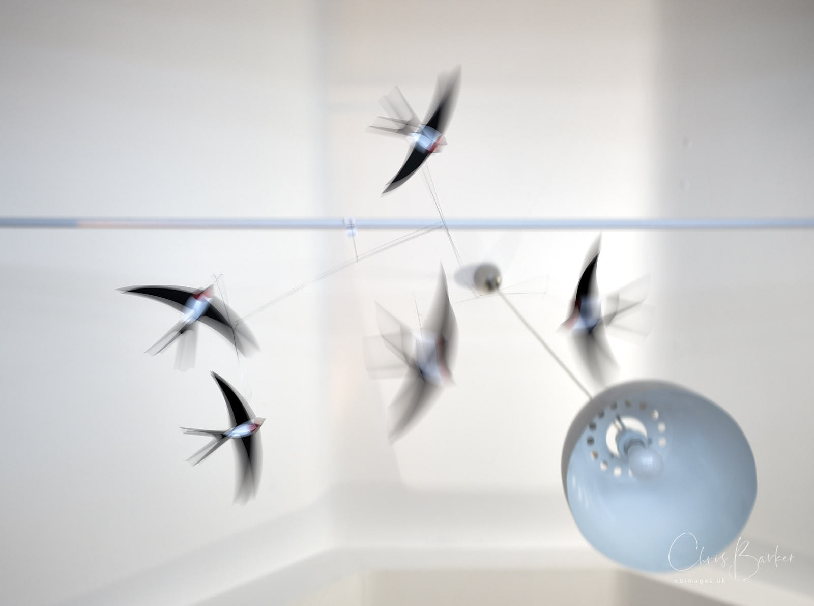 Blurred model swallows on a mobile above the photographer