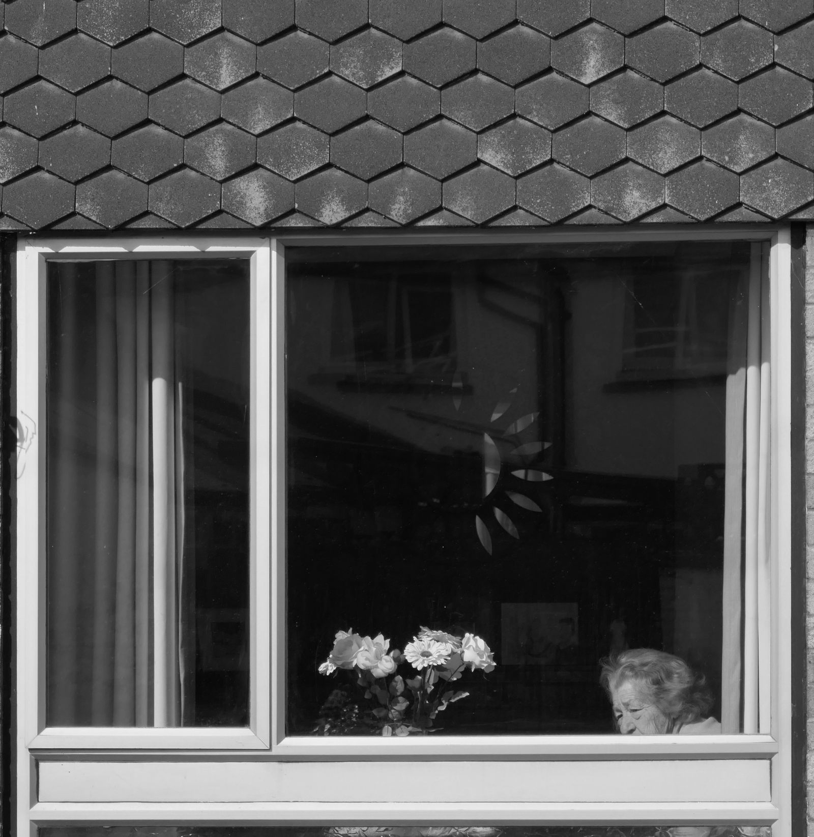 A lady peers from her front room window.