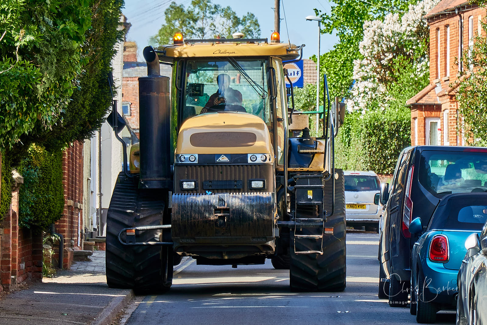 Large track-laying tractor squeezing down a narrow street.