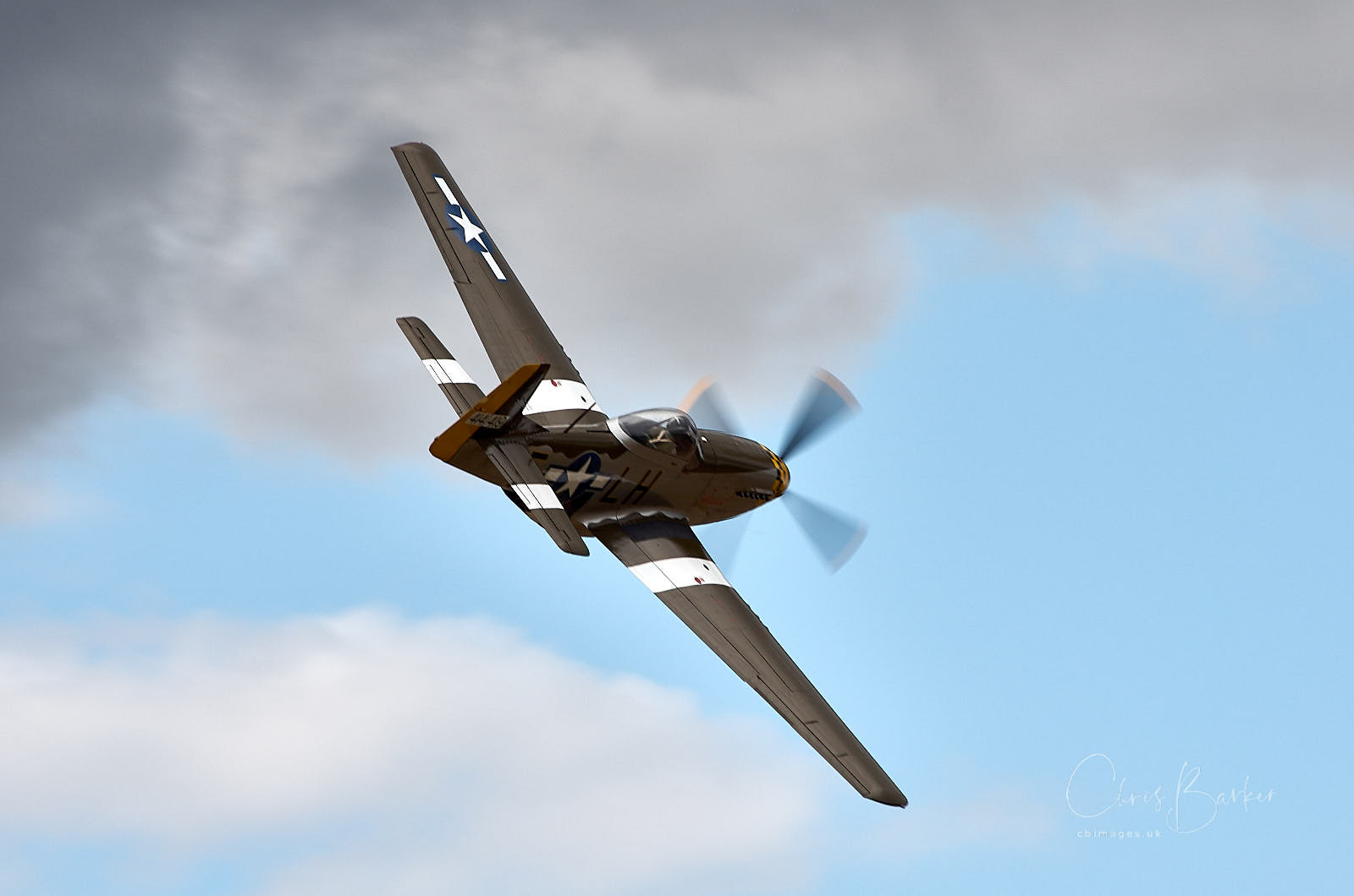A P-51 Mustang flying towards a blue sky